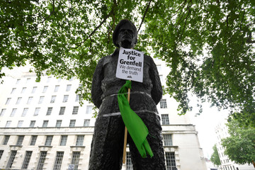 A banner is seen taped to a statue in Westminster as protesters from Justice4Grenfell demonstrate outside Downing Street in central London