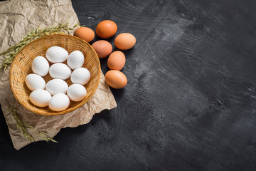 Chicken eggs in the basket on black wooden background. Copy space