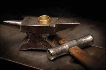 golden ring on an anvil and a goldsmith hammer in the jewelry workshop, still life with copy space in the dark background