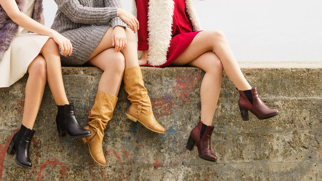 Three women presenting shoes outdoor
