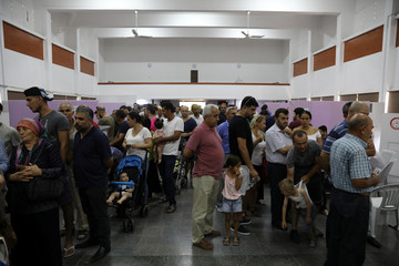 Turkish voters wait to cast their ballots for Turkey's presidential elections in the Turkish Cypriot northern part of the divided city of Nicosia