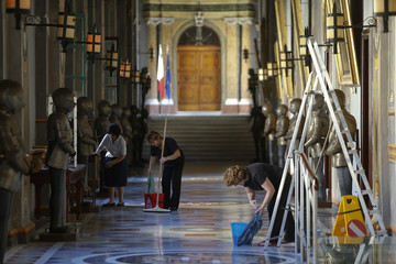 Cleaning staff work in a corridor in the Presidential Palace where the official dinner of the 5+5 Dialogue Summit will take place in Valletta