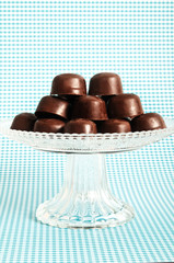 chocolate pralines on a glass stand with copy space