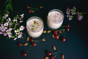 Two Glasses with a beautiful smoothies with nuts and flowers. View from above
