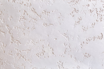 White plastered wall background with abstract pattern, close-up, macro.