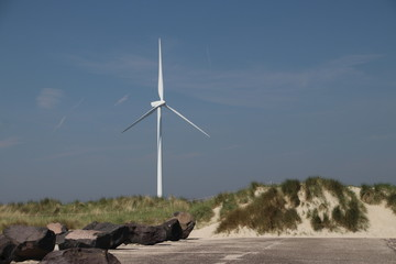 Modern windmill in the dunes at the coast of the North Sea in the Netherlands.