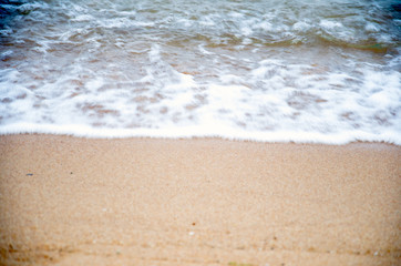 The beach with small waves and sand.