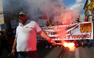 A man with a flare takes part in a national demonstration to show solidarity with migrants, after Soumaila Sacko a 29-year-old migrant agricultural worker, was shot and killed in southern Italy early this month, Rome