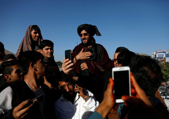 People take selfies with a Taliban in Kabul