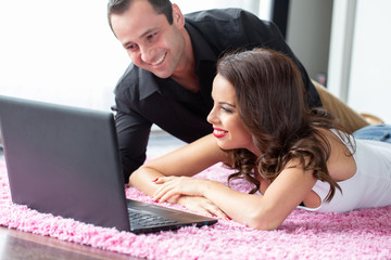 Happy young couple with laptop on carpet