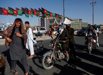 Taliban on motorbikes ride among people in Kabul