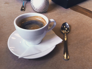 Breakfast in the cafe. Cup of Americano coffee in white mug, saucer and spoon. Close-up photo.