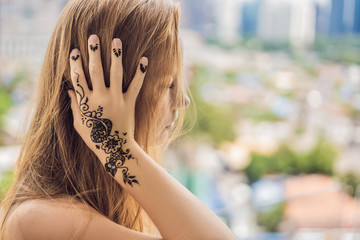 Portrait of a young woman in casual style with mehendi against the background of a big city