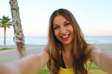 Cheerful young woman having fun taking selfie picture of herself on tropical beach in her travel holidays. Summer lifestyle.