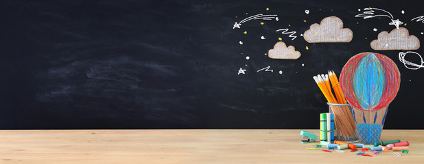 Back to school concept banner. hot air ballon and pencils in front of classroom blackboard.