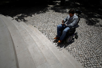 Wheelchair user Ricardo Teixeira uses phone app he developed to report accessibility infringements to authorities, while unable to proceed to the sidewalk, in Lisbon