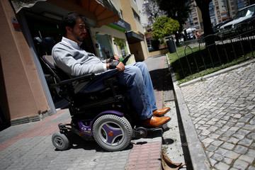 Wheelchair user Ricardo Teixeira demonstrates being unable to proceed to the sidewalk, in Lisbon