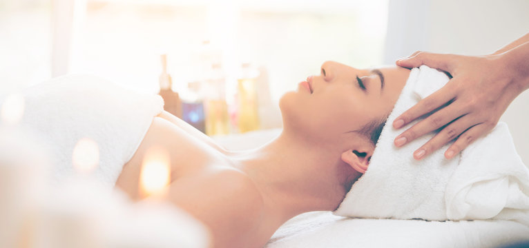Relaxed woman gets facial and head massage in spa.