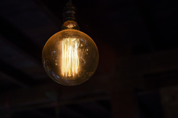 Design round tungsten light bulb on dark background, night light, energy and power concept
