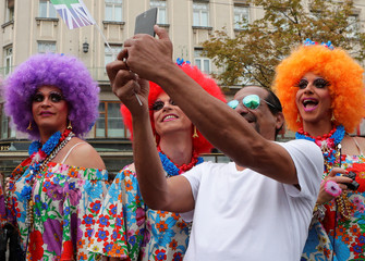 A spectator takes a selfie with revellers at Regenbogenparade gay pride parade in Vienna