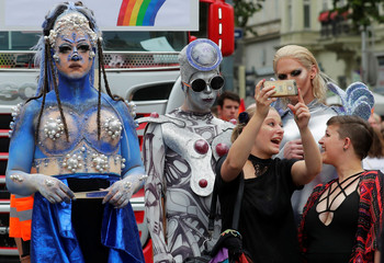 Spectators take selfies with revellers at Regenbogenparade gay pride parade in Vienna