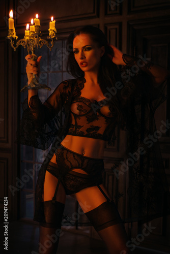 3a78d7cc717 Brunette woman in black lace lingerie with candelabrum posing on dark  background