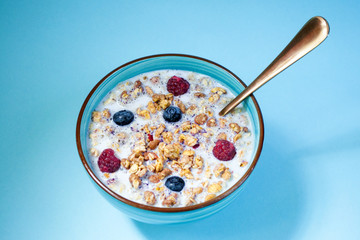 Bowl of healthy muesli for Breakfast with berries and milk, muesli, corn. On blue background