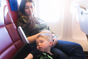 Young mother with sleeping 3 years old baby sitting together in airplane cabin near window. Child sleeps during the flight by plane