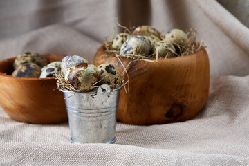 Rustic still life with quail eggs in bucket and bowls on a linen napkin over wooden background, selective focus