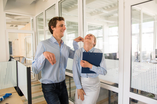 Smiling young man holding ear of laughing pretty woman while having fun in office