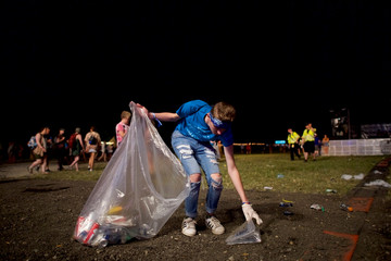 A worker collects refuse after Cold War Kids concert on the second day of the Firefly Music Festival in Dover, Delaware