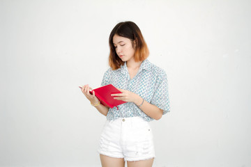 Portrait of thai adult beautiful girl short hair read red book