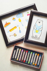 Crayons with two picture of bear and some cooking stuff with colored crayons. Flat lay