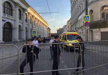 Policemen stand guard after a taxi ran into crowds of people in central Moscow