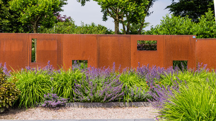 Garden design with a modern rusted metal garden screen and purple salvias