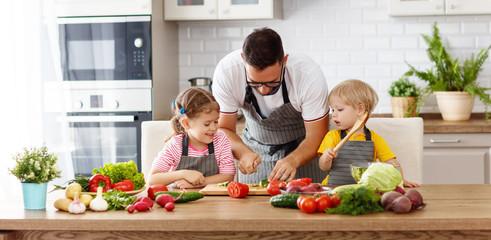 Keuken foto achterwand Koken father with children preparing vegetable salad