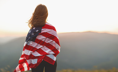 happy woman with flag of united states enjoying the sunset on nature