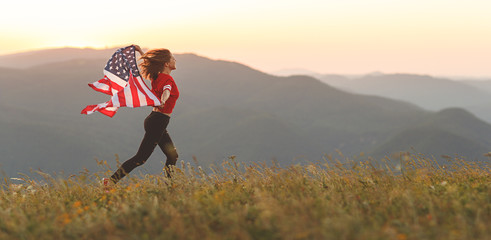 happy woman with flag of united states enjoying the sunset on nature Wall mural