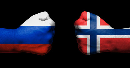 Flag of Norway and Russia painted on two clenched fists facing each other on black background/Norway–Russia relations concept