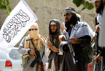Taliban walk as they celebrate ceasefire in Ghanikhel district of Nangarhar province, Afghanistan