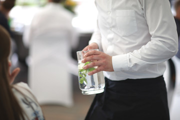 The waiter is holding a jug with a soft drink with fresh mint