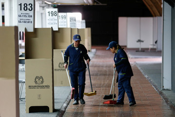 Workers clean in an polling station ahead of June 17 second round of presidential election in Bogota