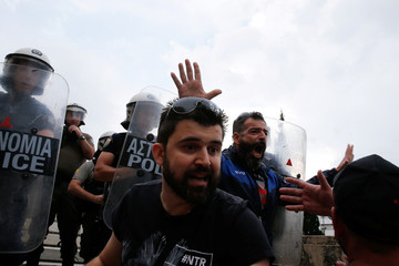 Protesters reacts in front of riot police during a demonstration against the agreement reached by Greece and Macedonia to resolve a dispute over the former Yugoslav republic's name, in Athens