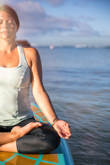 Cropped picture of woman in meditation after her SUP Yoga on the water