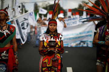 A woman dressed in an indigenous costume participates in the protest against privatization of water in San Salvador