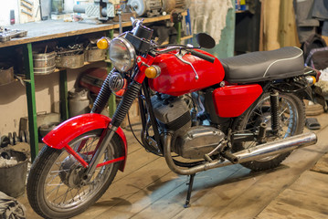 Red vintage motorcycle parked in the garage