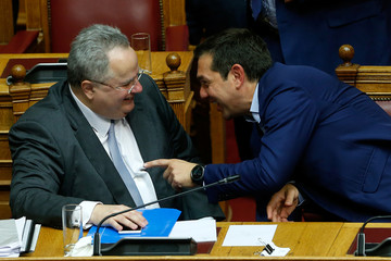 Greek Prime Minister Alexis Tsipras speaks with Greek Foreign Minister Nikos Kotzias during a parliamentary session before a vote following a motion of no confidence by the main opposition in dispute over a deal on neighbouring Macedonia's name, in Athens