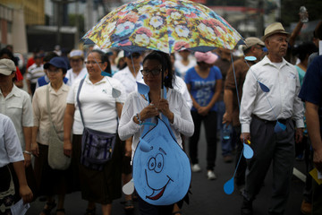 A woman participates in a protest against privatization of water in San Salvador
