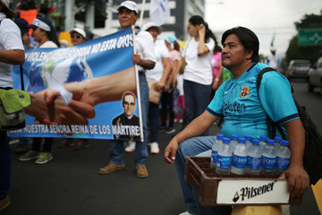A man sells bottled water during a protest against privatization of water in San Salvador
