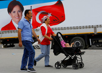 People walk past an election poster of Iyi (Good) Party leader Meral Aksener in Istanbul
